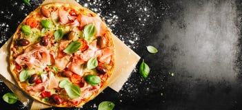 Pizza italiana tradizionale sulla tavola scura fotografia stock