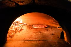 Pizza italienne étant faite cuire au four en four en bois traditionnel du feu de flamme Photos stock
