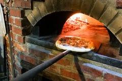 Pizza italienne étant faite cuire au four en four en bois traditionnel du feu de flamme Image stock