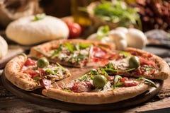 Pizza italienne avec de la salade de fusée sur la table en bois photo stock
