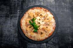 Pizza italienne avec différentes sortes de fromage sur une pierre et un panneau de craie rayé noir Nourriture traditionnelle ital photographie stock