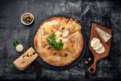 Pizza italienne avec différentes sortes de fromage sur une pierre et un panneau de craie rayé noir Nourriture traditionnelle ital image libre de droits