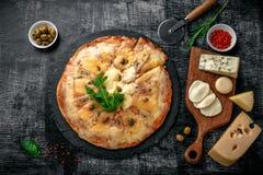 Pizza italienne avec différentes sortes de fromage sur une pierre et un panneau de craie rayé noir Nourriture traditionnelle ital images libres de droits