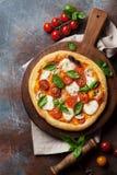 Pizza italienne avec les tomates, le mozzarella et le basilic image stock