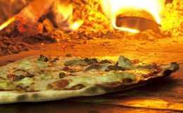 Pizza italienne dans un four brûlant en bois Image stock