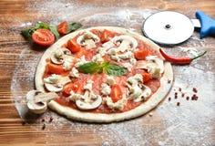 Pizza italienne faisant cuire le procédé de préparation sur la table en bois rustique Pâte de pizza et champignon de paris de cha image libre de droits