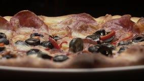 Pizza italienne rustique avec les pepperoni, le mozzarella et l'olive banque de vidéos