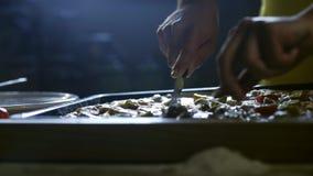 Pizza joven del corte del cocinero en los pedazos 4K almacen de metraje de vídeo