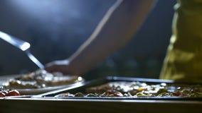 Pizza joven del corte del cocinero en los pedazos 4K metrajes