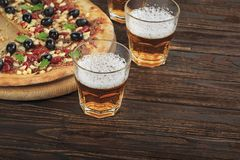 Pizza ?l, p? en tr?tabell, bar, pizzeria, sportst?ng, b?sta sikt som ?r hemlagad, pizza, mj?l, mozzarella, kavel arkivbild