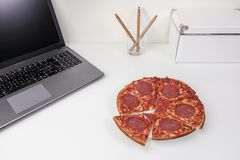 Pizza and laptop computer in white modern office workspace. stock photos