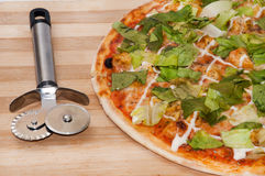 Pizza with letuce and pizza cutter on the wooden board.  Stock Photo