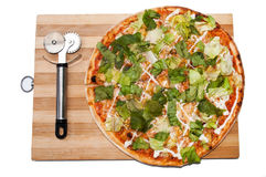 Pizza with letuce and pizza cutter on the wooden board.  Royalty Free Stock Photo