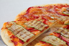 Pizza lifted slice. Italian vegetarian pizza lifted slice with pepper and zucchini stock photo