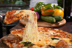 Pizza lifting slice on wooden board Stock Photography