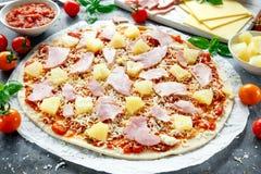 Pizza lista para guisar de Hawaii con el jamón y la piña, albahaca, tomates en el papel apoyado Imágenes de archivo libres de regalías
