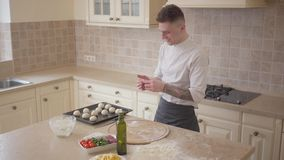 Pizza maker in cook uniform putting dough balls for pizza on baking tray in the kitchen. Food preparation concept. Top. Young skillful pizza maker in cook stock video footage