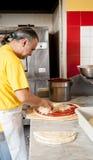 Pizza Maker puts mozzarella cheese on a pizza Stock Image