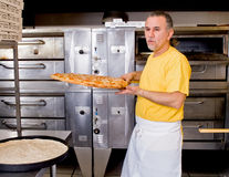 Pizza Maker removes  a Fresh  Pizza from the oven Royalty Free Stock Photos
