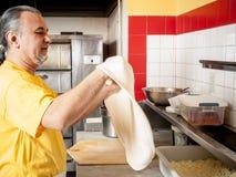 Pizza Maker twirls a Fresh  Pizza dough. In a pizza kitchen Stock Image
