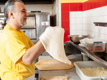 Pizza Maker twirls a Fresh  Pizza dough Royalty Free Stock Photography