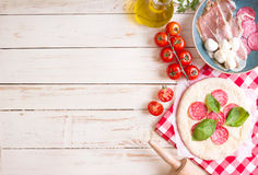 Pizza making background. Ingredients for making pizza. Space for text. Pizza dough, flour, cheese, mozzarella, tomatoes, basil, pepperoni, olives and rolling Royalty Free Stock Photo