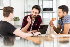 Pizza mangeuse d'hommes et son ami tenant une pièce d'or Cryptocurre Photographie stock libre de droits