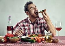 Pizza mangiatrice di uomini affamata pazza fotografia stock