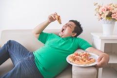 Pizza mangiatrice di uomini di peso eccessivo pigra mentre mettendo su uno strato fotografie stock