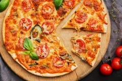 Pizza Margarita com tomates, mussarela e manjericão de cereja em uma placa de corte Elimine uma fatia de pizza A vista da parte s foto de stock