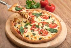 Pizza Margherita com tomates, mussarela e manjericão em um fundo de madeira, uma fatia de pizza com esticão do queijo Fotos de Stock