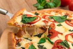 Pizza Margherita con i pomodori, la mozzarella ed il basilico su un fondo di legno, una fetta di pizza con l'allungamento del for Fotografia Stock