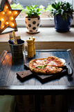Pizza Margherita freshly baked on a table in cafe Stock Photos