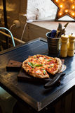 Pizza Margherita freshly baked on a table in cafe Stock Photography