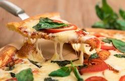 Pizza Margherita mit Tomaten, Mozzarella und Basilikum auf einem hölzernen Hintergrund, eine Scheibe der Pizza mit dem Käseausdeh Lizenzfreie Stockfotos