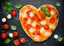 Pizza Margherita shaped heart with cherry tomatoes, mozzarella a Stock Images