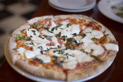 Pizza Margherita sitting on a table at a restaurant Stock Images