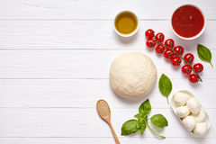 Pizza margherita traditional preparation recipe with baking ingridients: raw dough, cherry tomatoes, basil, tomato sauce Stock Images