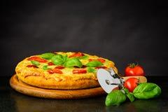 Pizza Margherita y rueda del cortador fotografía de archivo