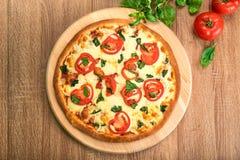 Pizza Margherita z pomidorami, mozzarellą i basilem na drewnianej desce, mieszkanie nieatutowy Obraz Stock