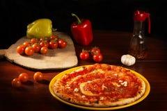 Pizza marinara with garlic and tomatoes. Pizza with marinara sauce, oil, peppers and garlic on wooden table royalty free stock photography