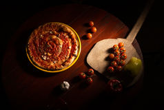 Pizza marinara with garlic and tomatoes on wooden paddle. Pizza with marinara sauce, peppers and garlic on wooden table royalty free stock image