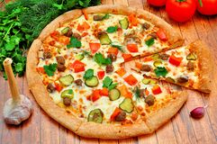 Pizza with meat, cucumbers, tomatoes and greens Royalty Free Stock Image