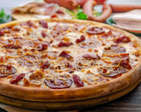 Pizza meat feast 2. Pizza meat feast with ham and salami on wooden table Stock Photo