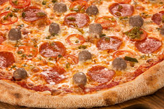 Pizza with meatballs, mozzarella, pepperoni, pickled cucumbers, cherry tomatoes Stock Photography