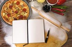 Pizza med anteckningsboken och ingredienser arkivbilder