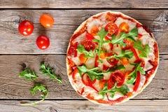 Pizza med arugula och körsbärsröda tomater mot lantligt trä arkivfoto