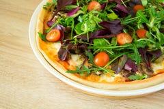 Pizza med arugula, salladblandningen och körsbärsröda tomater Royaltyfria Bilder