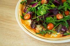 Pizza med arugula, salladblandningen och körsbärsröda tomater Arkivfoton