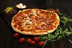 Pizza med bacon, korvar, skinka, tomaten och oliv Stänk med arugula och som tjänar som med tomaten och ost Pizzarestaurang Royaltyfri Bild